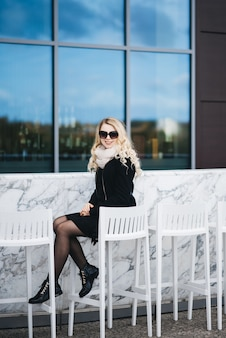 Beautiful attractive blonde girl sitting behind a white marble bar counter with high chairs on the background of a modern building in minimal style