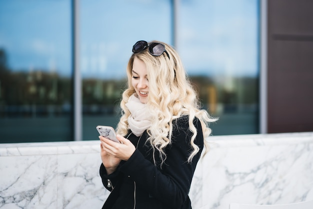 Beautiful attractive blonde girl sitting behind a white marble bar counter with high chairs on a modern building in minimal style