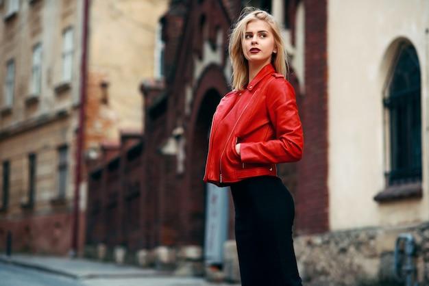 赤い革のジャケットとタイトな黒のスカートで完璧な体型の美しい魅力的なブロンドの女の子