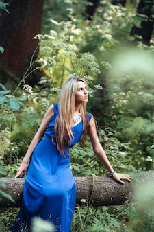 Beautiful attractive blonde in a long blue dress alone in the forest. woman sitting in a tree and dreams
