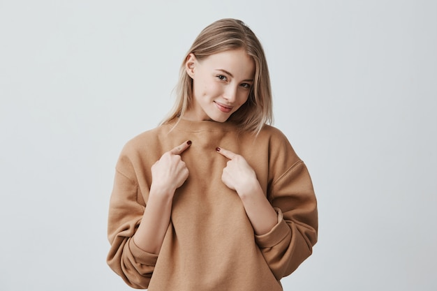 Красивая привлекательная блондинка улыбается, указывая указательными пальцами на себя, одетая в бежевый свитер с длинными рукавами, выражая положительные эмоции и чувства.