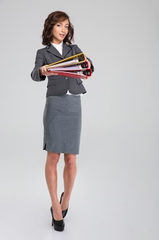 Beautiful attractive curly young businesswoman giving folders to you