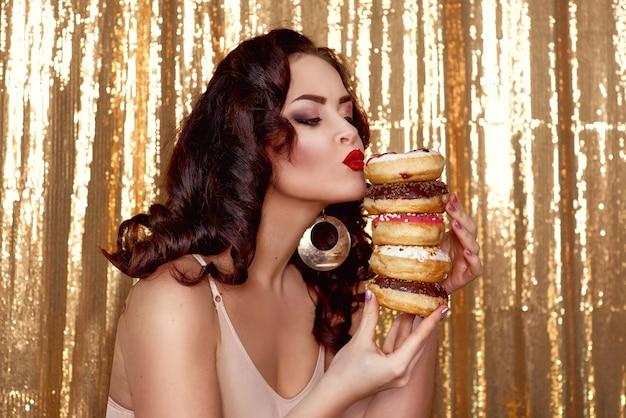 다채로운 맛있는 글레이즈드 도넛을 가진 아름다운 매력적인 검은 머리 여자