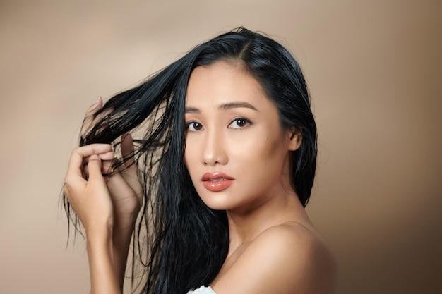 Красивая привлекательная элегантная азиатская женщина рукой трогает лицо модели позы на студийной фотосессии, изолированной на белом фоне