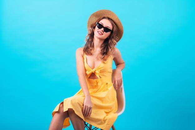 ファッショナブルな明るい黄色のドレス、サングラス、1トンの青い背景に麦わら帽子をかぶった、魅力的な笑顔の美しく魅力的なヨーロッパの女の子。コピースペース、テキストまたは広告の場所、宣伝