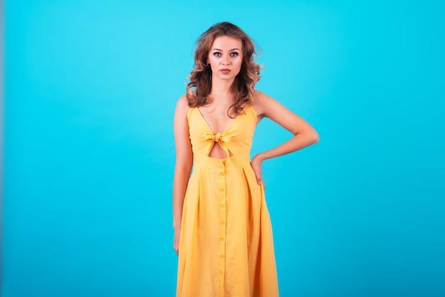 ファッショナブルな明るい黄色のドレスノン1トンの青い背景で、魅力的な笑顔で美しく、魅力的なヨーロッパの女の子。コピースペース、テキストまたは広告の場所、宣伝