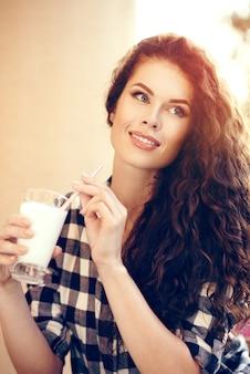Красивая привлекательная модная женщина с вьющимися волосами пьет молочный коктейль летом в городе
