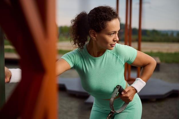静止した屋外ケーブルクロスオーバーで上腕三頭筋と肩の筋肉の運動をしているアフリカ系アメリカ人の民族の美しい魅力的なフィットの女性。スポーツ分野で運動するアスリートを決定する