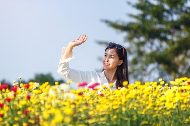 공원에서 화려한 꽃과 함께 아름 다운 매력적인 여자 프리미엄 사진