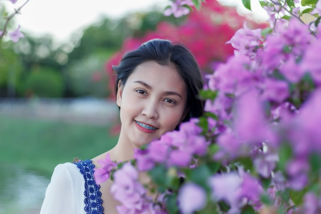 Beautiful attractive girl with colorful flower in park