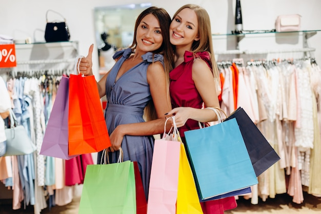 Beautiful, attractive girlfriends with colored bags in the showroom