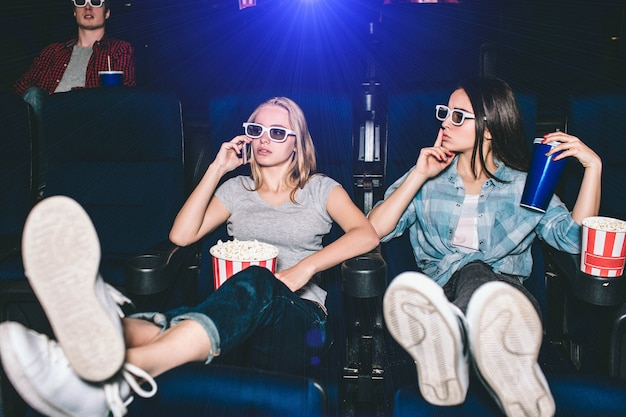 Beautiful and attractive girls are sitting in chairs. blonde girl is talking on thhe phone. her friend is showing the silence symbol. she wants her to be quiet and stop talking during watching movie.