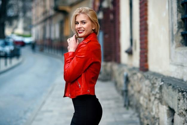 赤い革のジャケットとタイトな黒のスカートの理想的な姿で美しい魅力的な笑顔のブロンドの女の子は、日没で彼女の髪に彼女の手に触れる