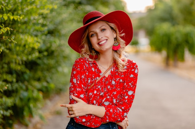 Beautiful attractive stylish blond smiling woman in straw red hat and blouse summer fashion outfit