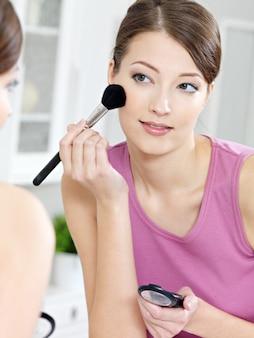 Bella donna attraente che applica ombretto con il pennello guardandosi allo specchio