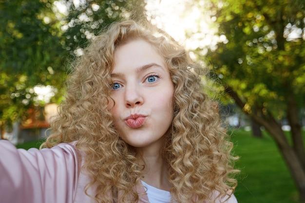 Красивая привлекательная женщина-блондинка с вьющимися волосами и очаровательными голубыми глазами, отправляет воздушный поцелуй и делает селфи