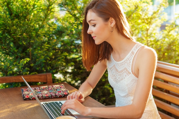 Beautiful attractive woman at the cafe with a laptop having a coffee break