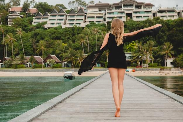 Bella donna attraente vestita in abito nero in posa sul molo in hotel resort di lusso, vacanze estive, spiaggia tropicale