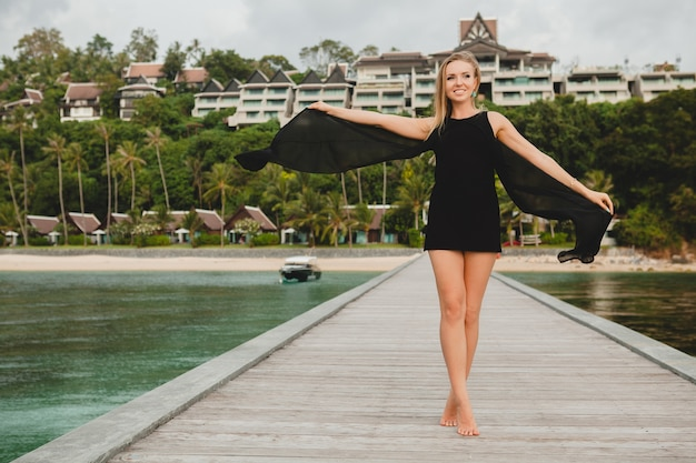 Beautiful attractive woman dressed in black dress posing on pier in luxury resort hotel, summer vacation, tropical beach