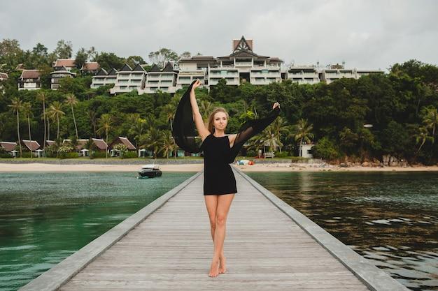 高級リゾートホテル、夏休み、熱帯のビーチの桟橋でポーズをとって黒いドレスに身を包んだ美しい魅力的な女性