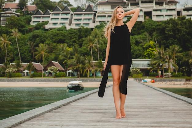 Bella donna attraente vestita in abito nero romantico in posa sul molo in hotel resort di lusso,