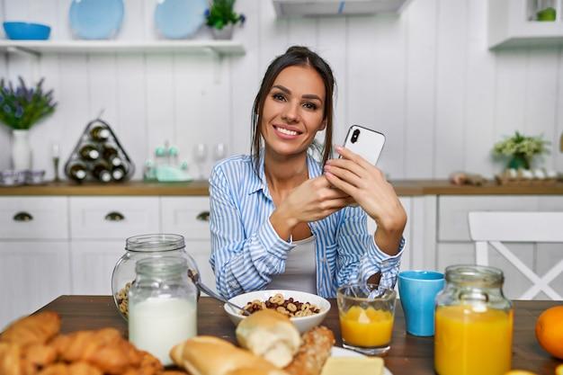 朝食を食べる美しい魅力的な女性。週末に牛乳とシリアルを食べて、電話でカメラを見ている女の子