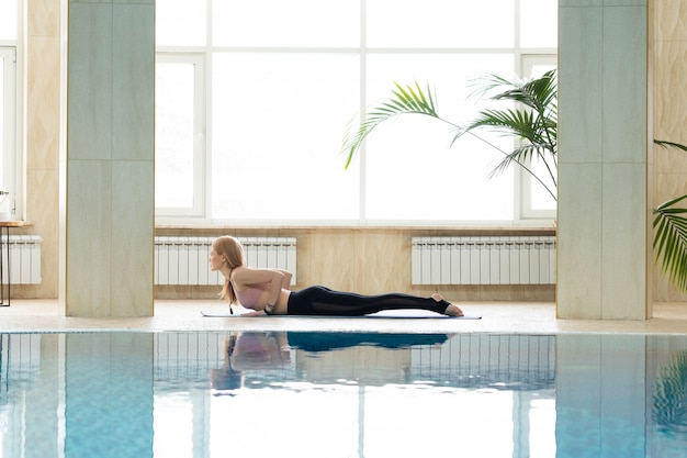 Beautiful attractive woman practice yoga pose on the pool in the morning, relax in holiday or day off.