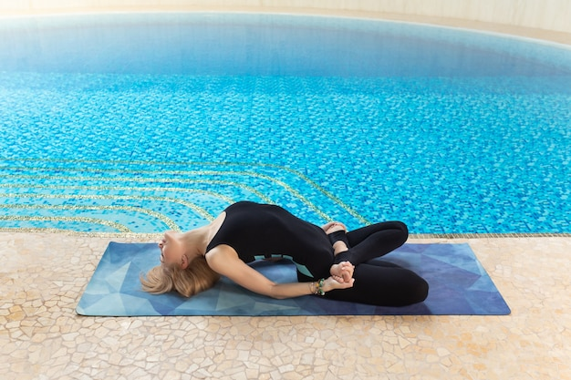 Beautiful attractive woman practice yoga pose on the pool in the morning, relax in holiday or day off