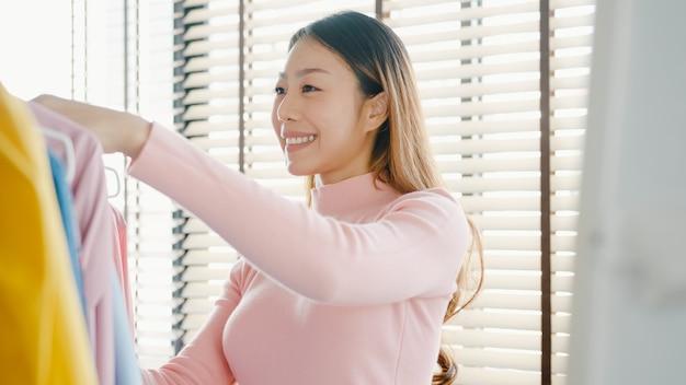 집이나 상점에서 옷장에 그녀의 패션 복장 옷을 선택하는 아름 다운 매력적인 젊은 아시아 아가씨.