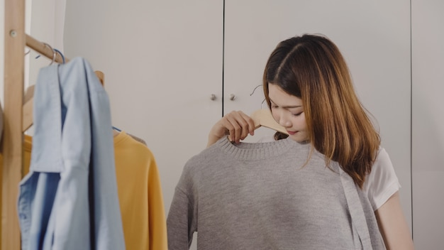 Beautiful attractive young asian woman choosing her fashion outfit clothes in closet at home