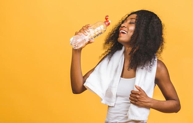 Красивые привлекательные молодые потные афро-американские пьют воду после тренировки