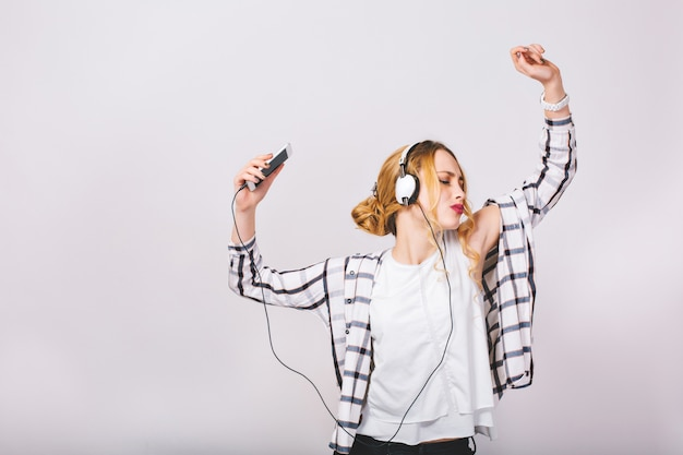 Beautiful attractive young woman in casual plaid shirt and white blouse listening to music and dancing. cheerful pretty girl having fun near grey wall. closed eyes. joyful. happyness.