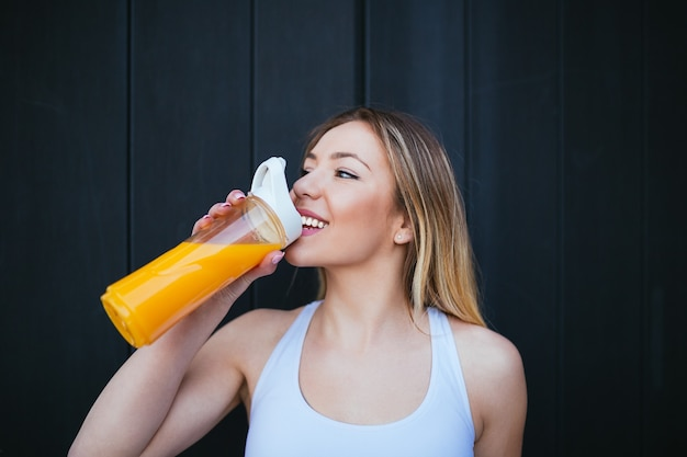健康的な新鮮なオレンジジュースを屋外で飲む美しい魅力的な若い女性。健康的なライフスタイルのコンセプト。
