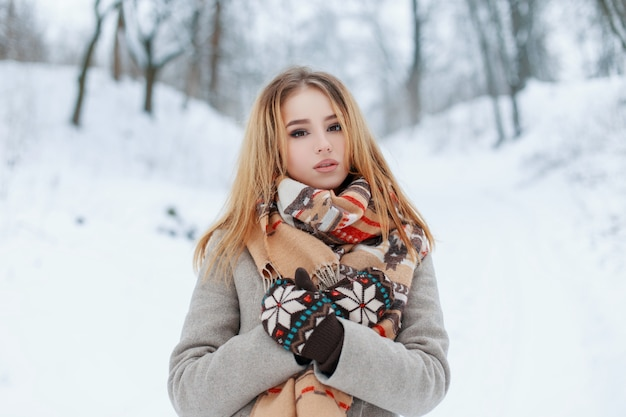 Beautiful attractive young woman in a fashionable gray coat in knitted vintage mittens with a stylish beige scarf with a pattern rest in a snowy park on a winter cold day. charming girl blonde.