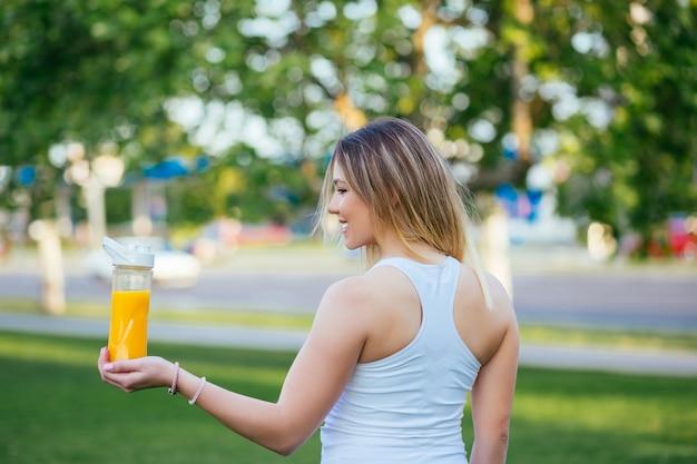 健康的な新鮮なオレンジジュースを屋外で保持している美しい魅力的な若い女性。健康的なライフスタイルのコンセプト。