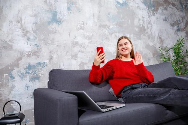 美しい魅力的な若い女性は、自宅のソファに座って電話で作業しています。彼女はラップトップの横にある赤いセーターとジーンズを着ています