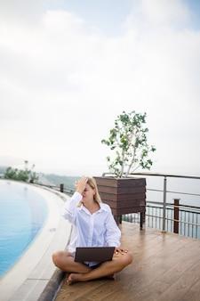 美しい魅力的な若い女性は大きなプールの近くに座って、ラップトップで働いています。休暇中のリモートワーク。