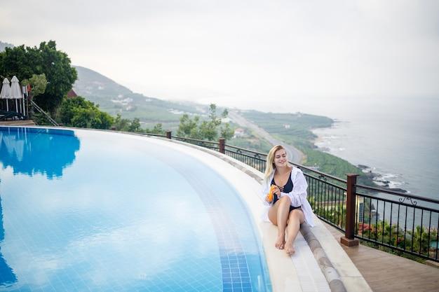 海を見下ろす大きなプールの近くに座っている美しい魅力的な若い女性。休暇の概念。黒い水着の女の子が日焼け止めで肌を塗ります