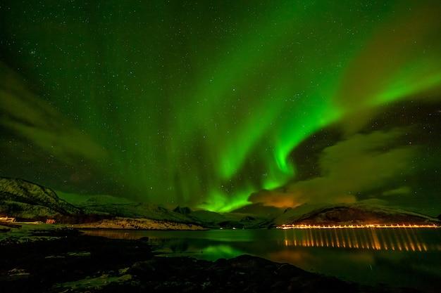 北ヨーロッパの山々の向こうにある美しいオーロラ、極光