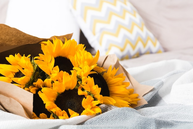 Beautiful authentic yellow sunflowers bouquet with craft paper in bed