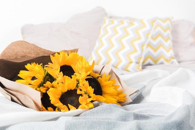 ベッドのクラフト紙と美しい本物の黄色のヒマワリの花束