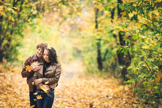 Beautiful autumn alley of maples loving couple embrace and yellow leaves fall on them