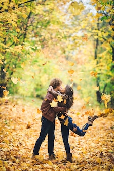 Beautiful autumn alley of maples loving couple kisses and yellow leaves fall on them