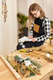나무 테이블에 마른 꽃의 아름다운 가을 꽃다발과 배경에 귀여운 젊은 꽃집 여자