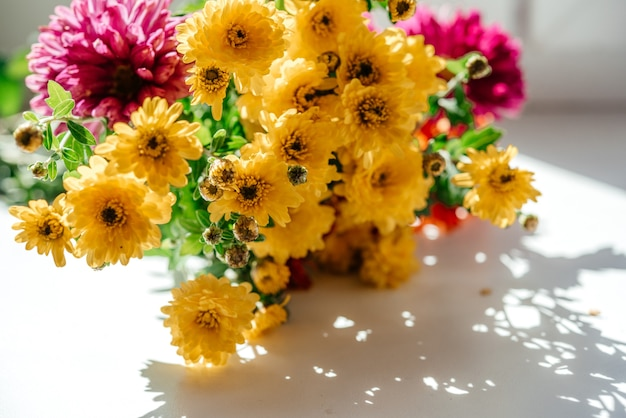 창턱에 노란 아스터와 국화 꽃의 아름다운 가을 꽃다발