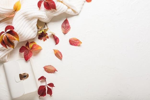 白いテーブルの背景に服と美しい秋の構成
