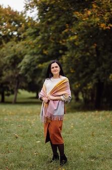 아름 다운가 여자 초상화입니다. 노란색 위에 포즈 젊은 여자 가을 공원에서 나뭇잎. 집 밖의