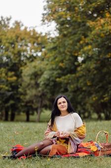 美しい秋の少女の肖像画。秋の公園で黄色の葉の上にポーズをとる若い女性。アウトドア