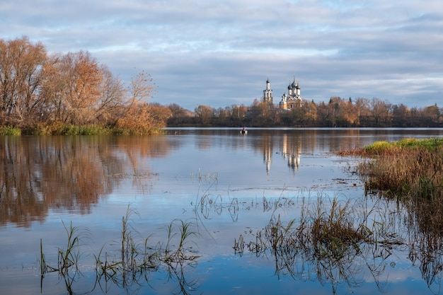 Beautiful autumn landscape in view of the orthodox church on the river bank . the village of dedinovo, moscow region