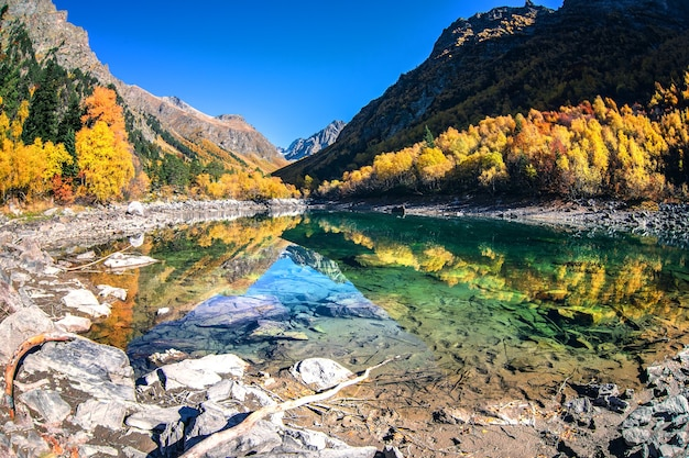 Beautiful autumn landscape with clear green water of a mountain lake and reflected trees with autumn foliage and mountain peaks